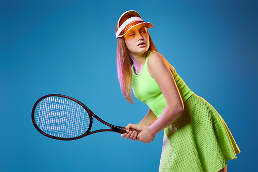 girl teenager with racket in sporswear and hat