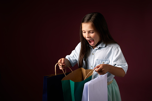 happy little child girl holds many shopping bags