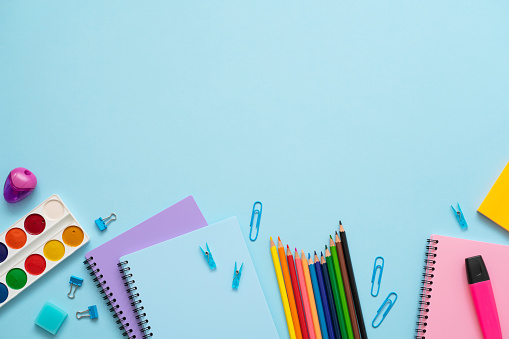 Bright colourful school stationery on the blue background. Top view of blue, purple and pink notebooks, color pencils, watercolor, paper clips, marker and eraser. Copy space